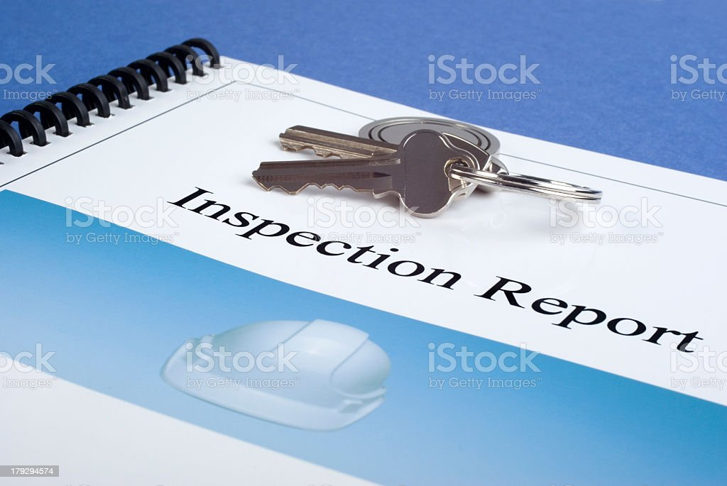 A set of two keys on a ring and a inspection report folder stock photo
