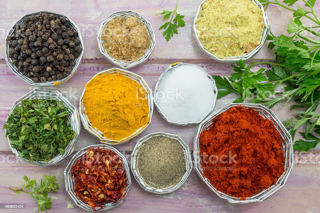 Set of various spices in shiny bowls on purple table stock photo