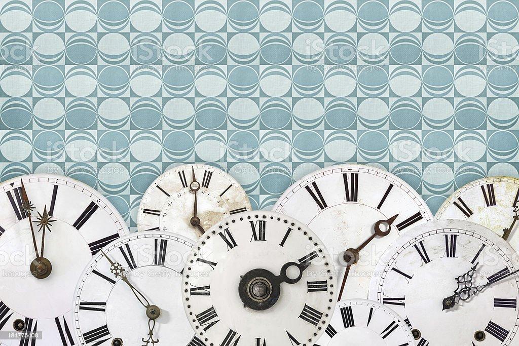 Set of vintage white clock faces against a blue retro wallpaper...