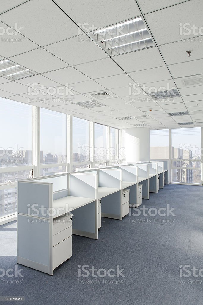 Set of white cubicles facing a window on gray floor stock photo