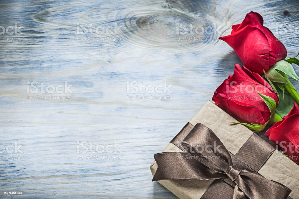 Set of wrapped present box red roses on wooden board celebration stock photo