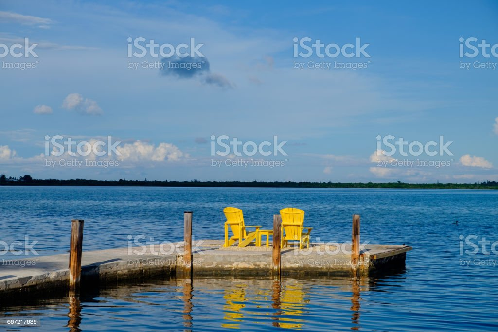 A set of yellow adirondack chairs sit at the end of a wooden and concrete in the florida keys at the end of the beautiful sunny day on vacation stock photo
