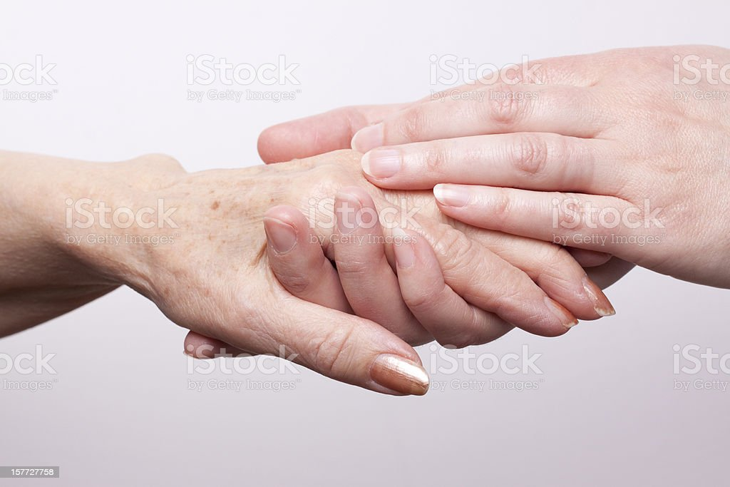 A set of younger hands holding the hand of an older woman royalty-free stock photo