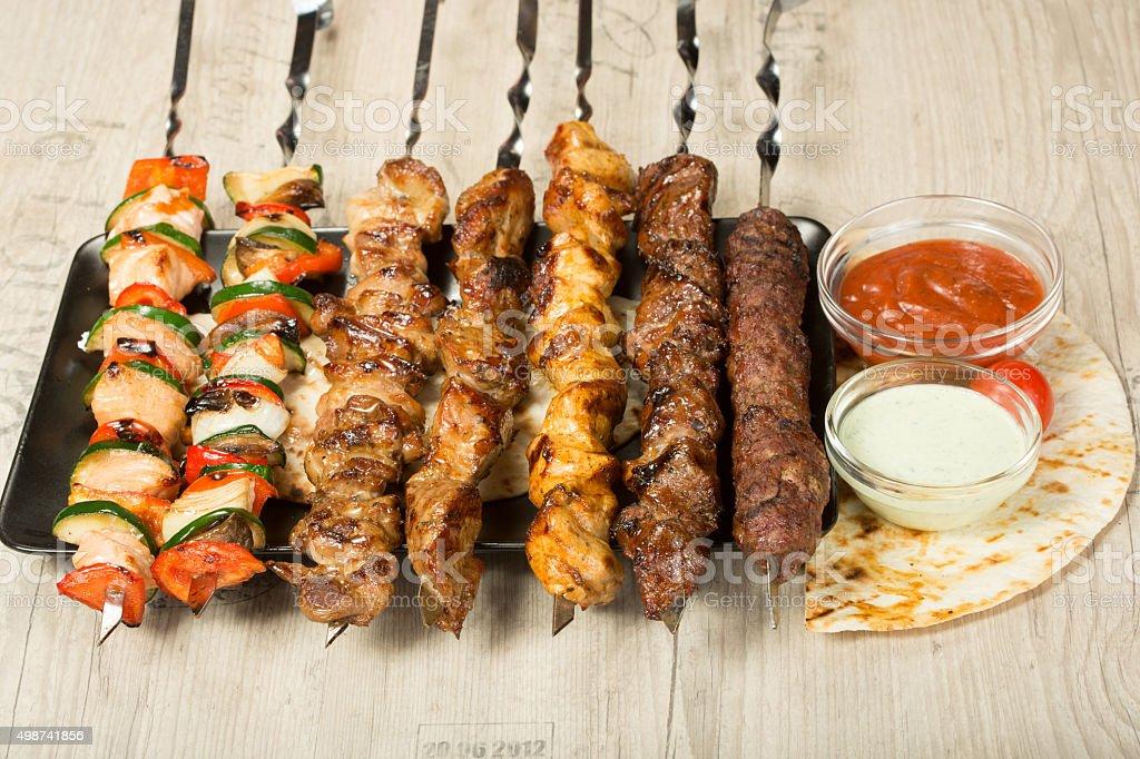 set shashlik. kebab skewer, black rectangular plate. sauce and onions stock photo