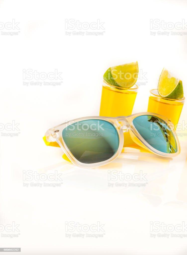 set shot drinks, yellow kamikaze drinks decorated with fruit, lime, sunglasses stock photo