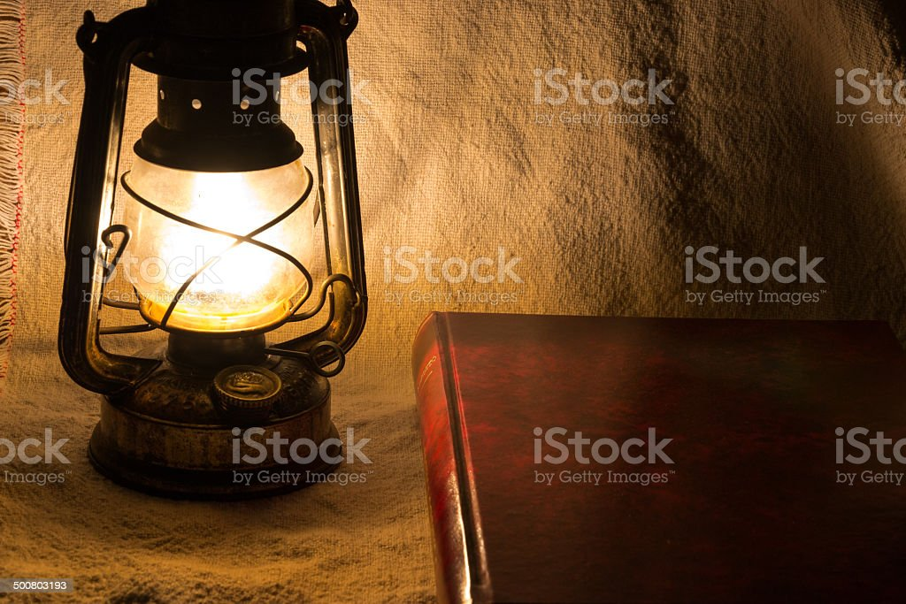 Set with an old rusty lantern and a book stock photo