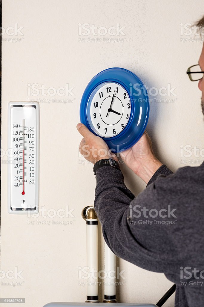 Setting a clock by one hour for daylight savings stock photo