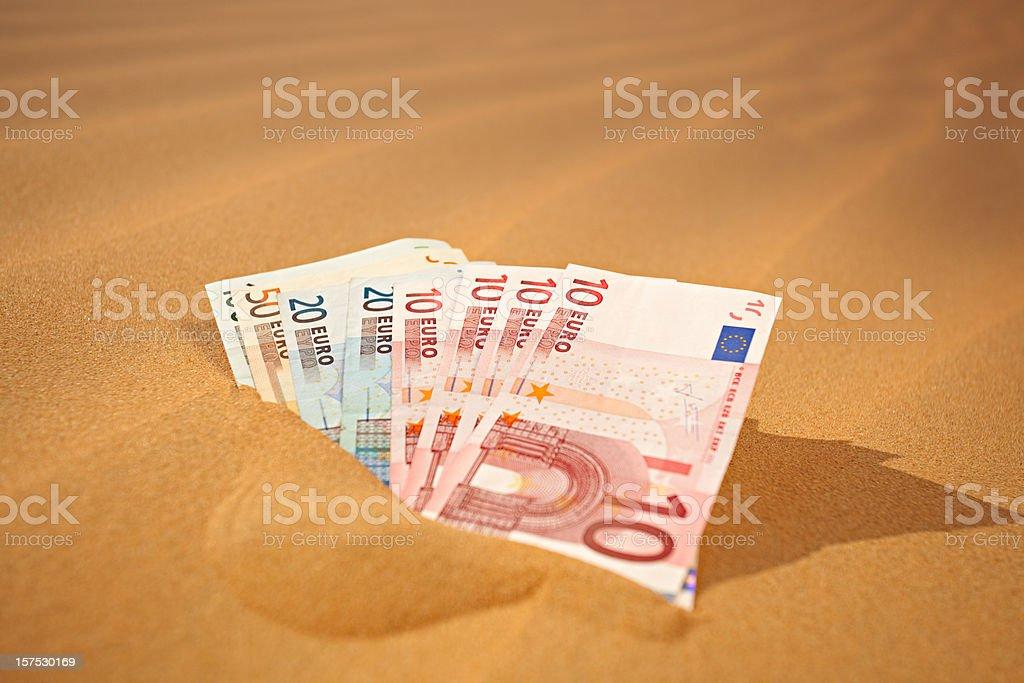 setting money into sand - german phrase royalty-free stock photo