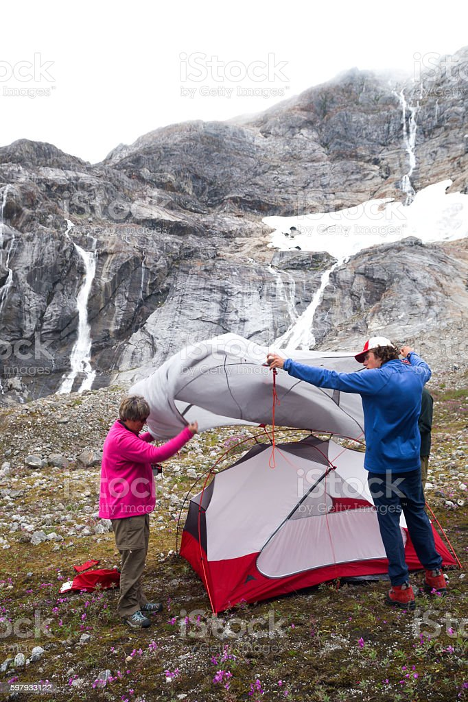 Setting up a tent for overnight camping on glacier stock photo