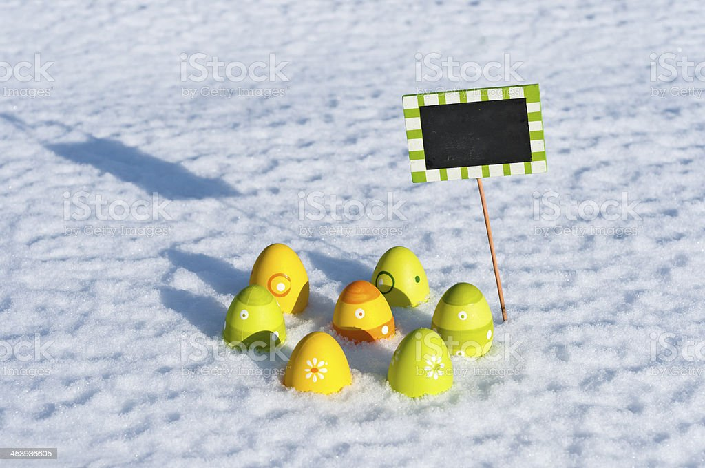 Seven colorful easter eggs in the snow stock photo