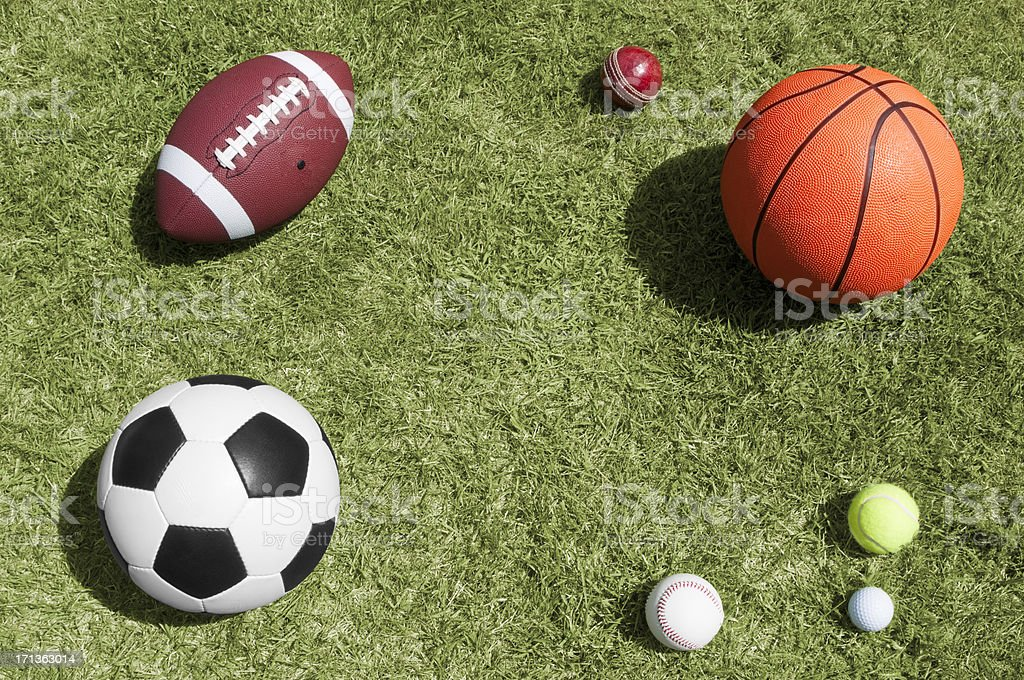 Seven different sports balls lying on a grass background royalty-free stock photo