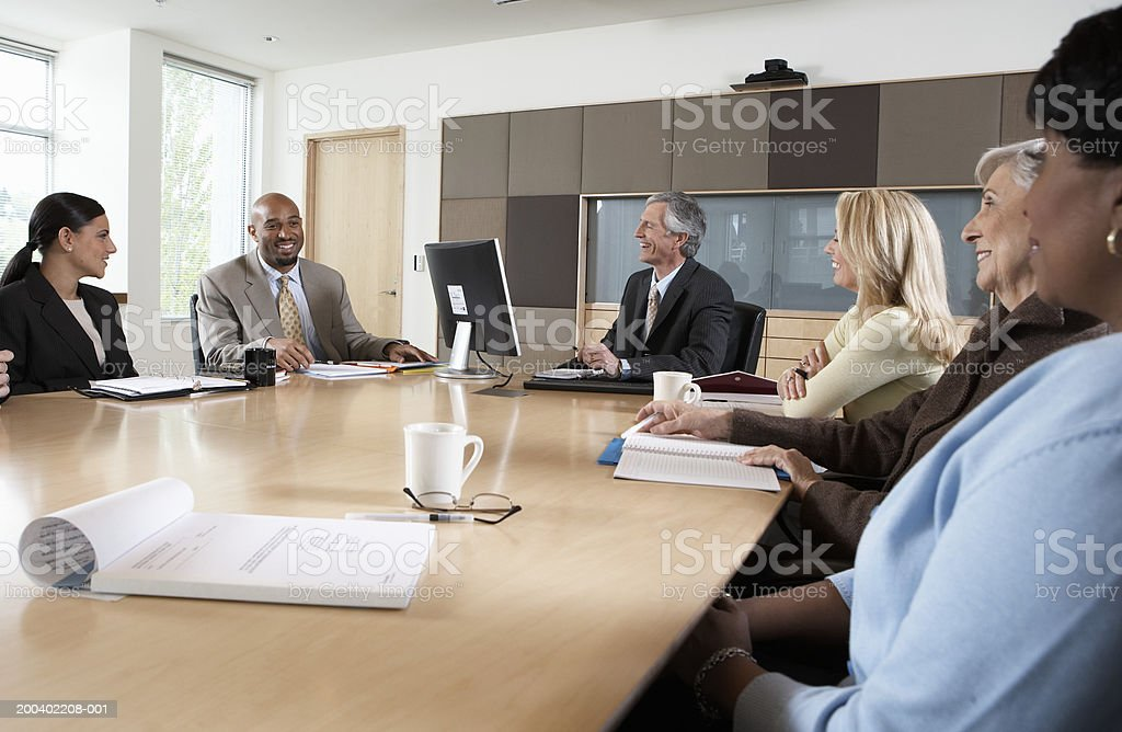Seven executives meeting in boardroom, smiling royalty-free stock photo