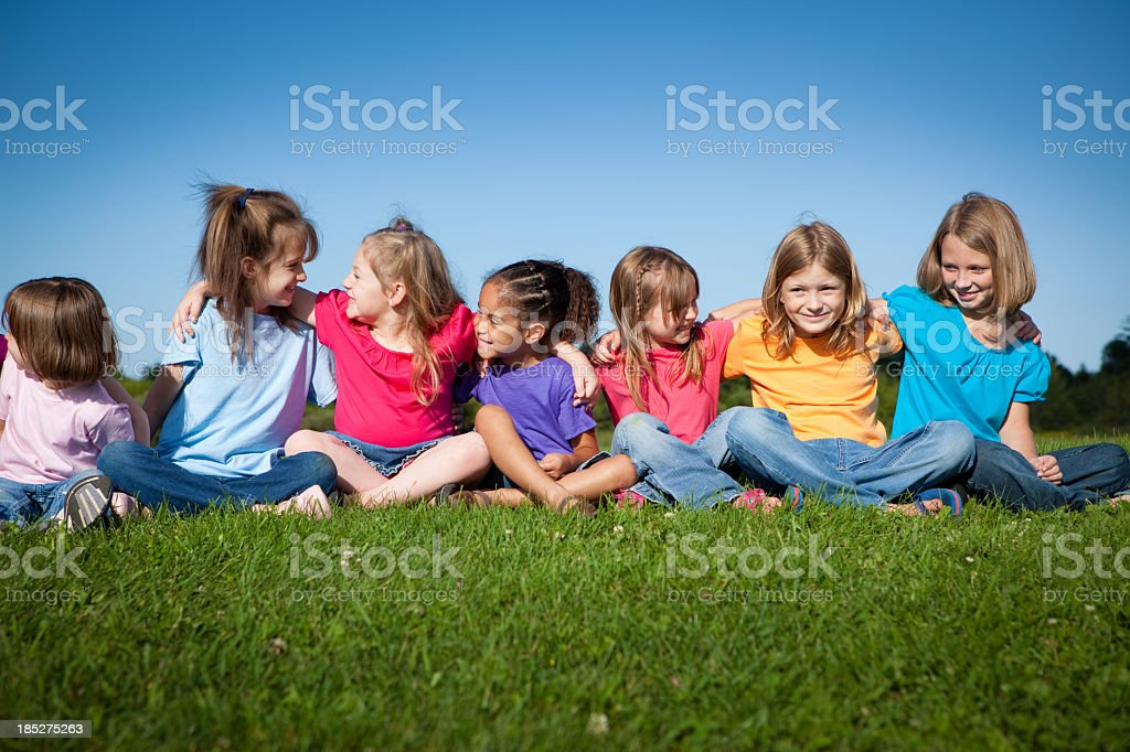 Seven Happy Little Girls Sitting and Hugging One Another royalty-free stock photo