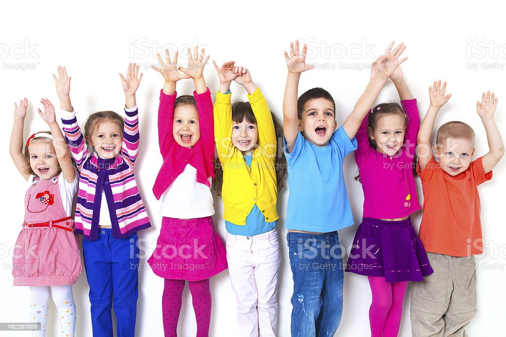 Seven kids in colorful clothing raising their both hands up stock photo