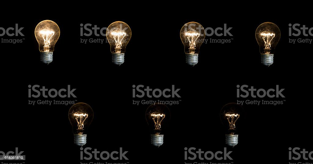 Seven lightbulbs on black background stock photo