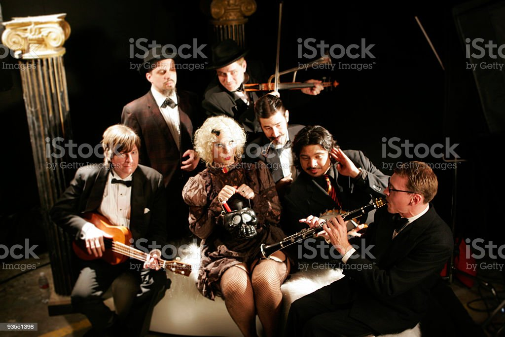Seven musicians posed with instruments, in dressy attire  stock photo