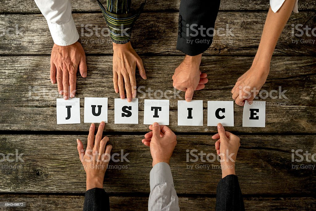 Seven people assembling the word Justice with white cards stock photo