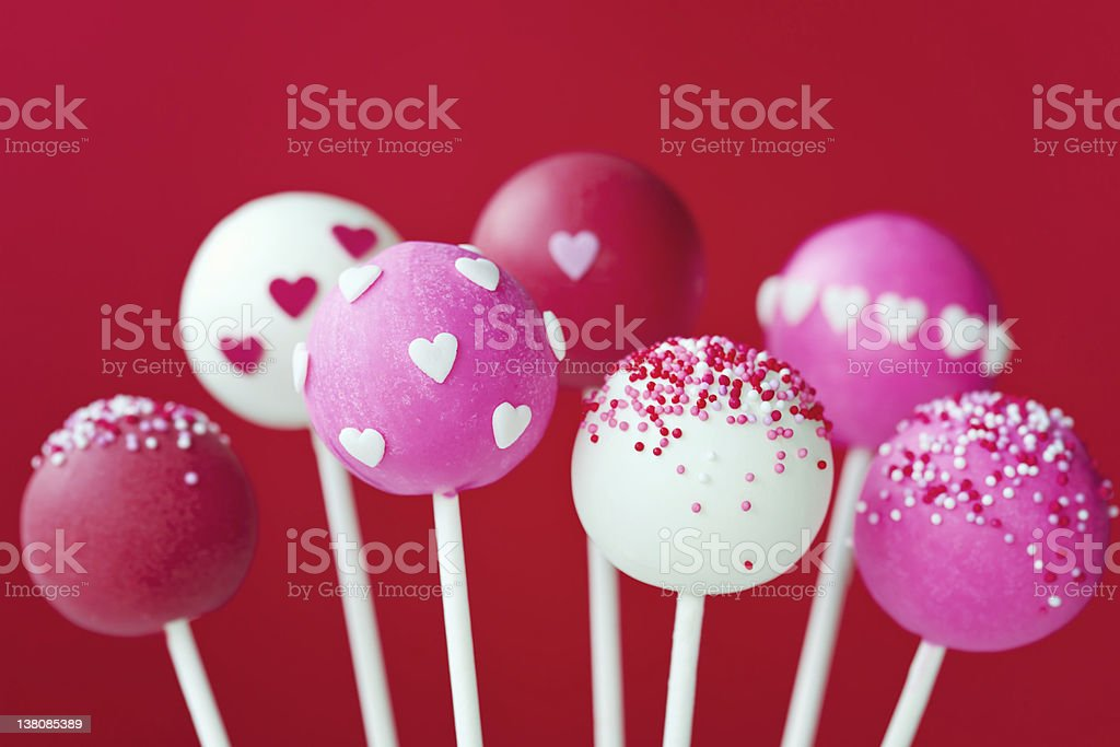 Seven pink and white Valentine cake pops on sticks stock photo