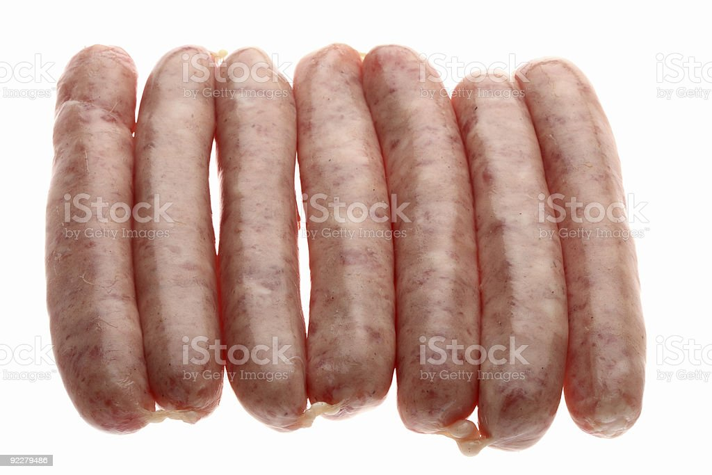 seven raw chipolata sausages on a white background stock photo