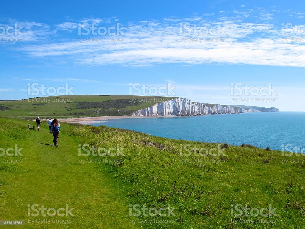 Seven Sisters England distant hikers on grassy path white cliffs stock photo