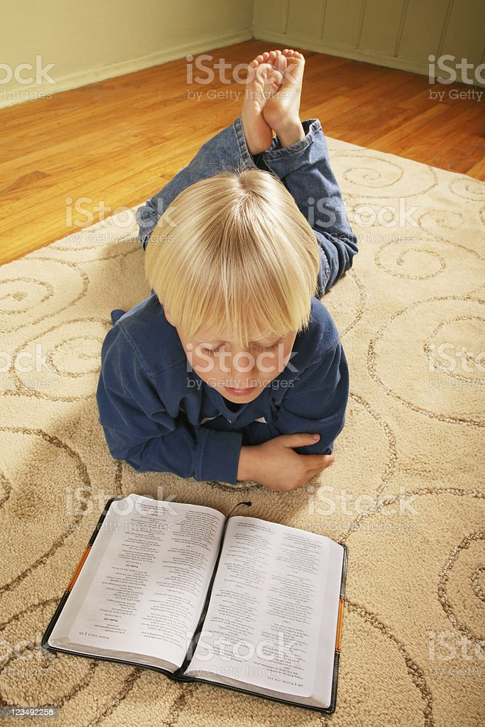 seven year old boy reading the bible stock photo