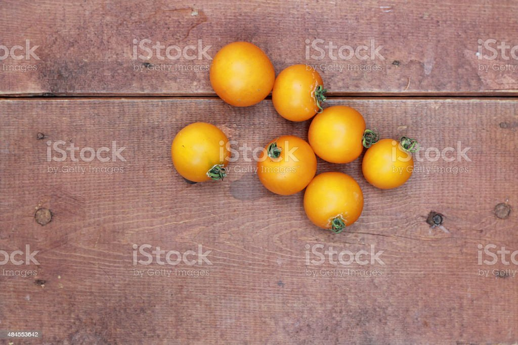 Seven Yellow Cherry Tomatoes on wood background stock photo