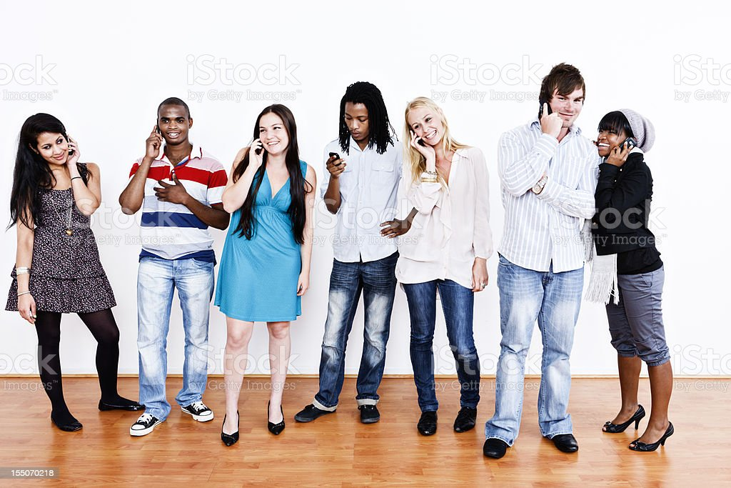Seven young people with must-have accessory, the mobile phone! royalty-free stock photo