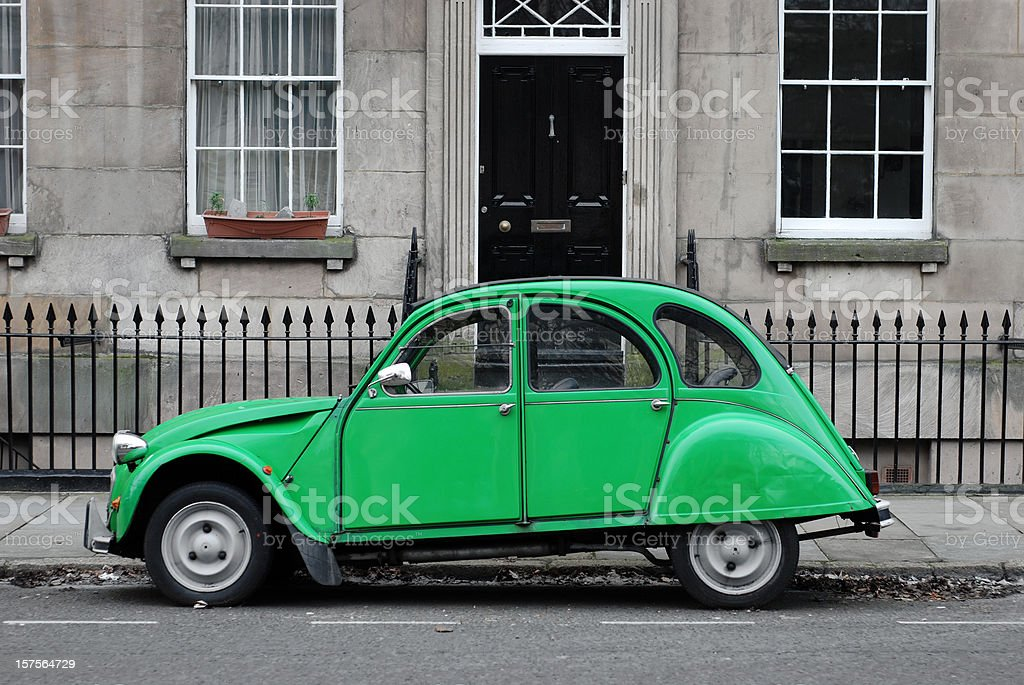 Seventies green car in front of house stock photo