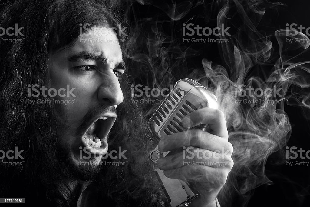 Seventies rock star singing on old fashioned microphone in smoke stock photo