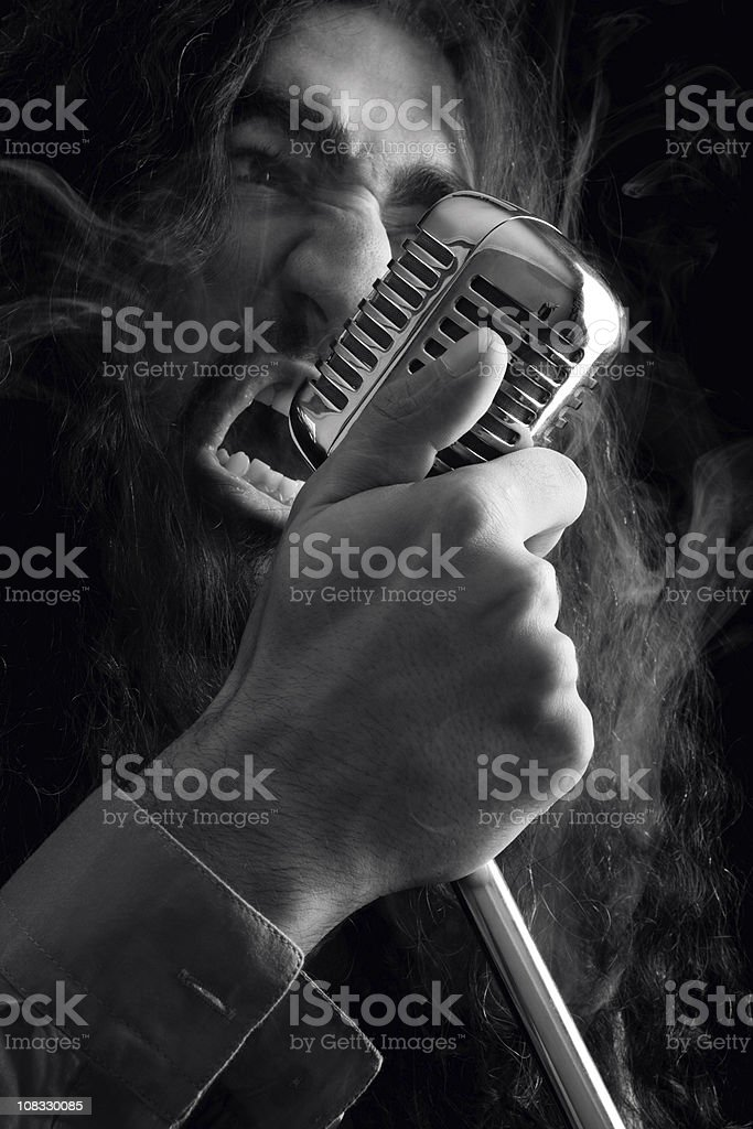 Seventies rock star singing on old fashioned microphone stock photo