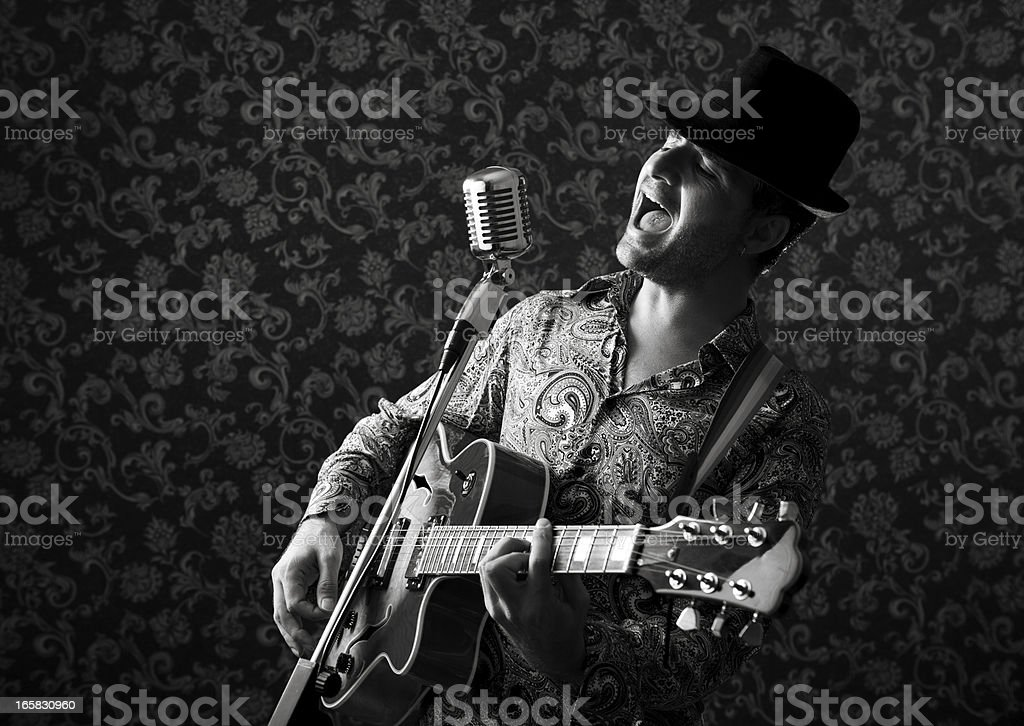 Seventies rock star with electro guitar singing on old-fashioned microphone stock photo