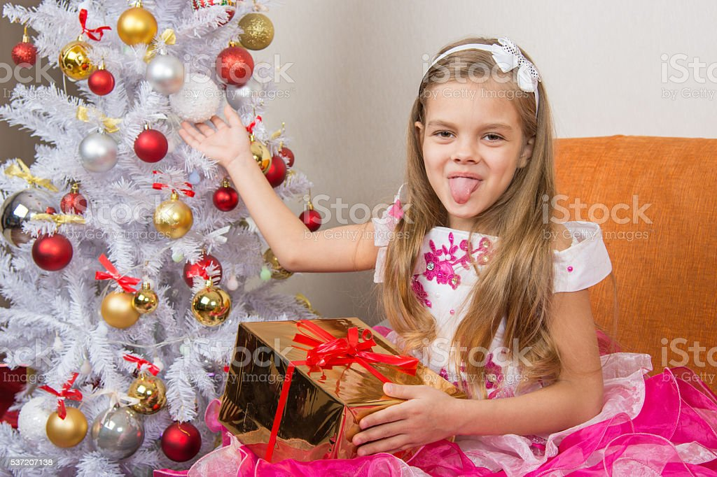 Seven-year girl in a beautiful dress sits with a gift stock photo