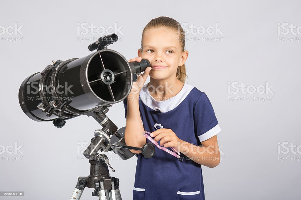 Seven-year girl standing next to a reflector telescope stock photo