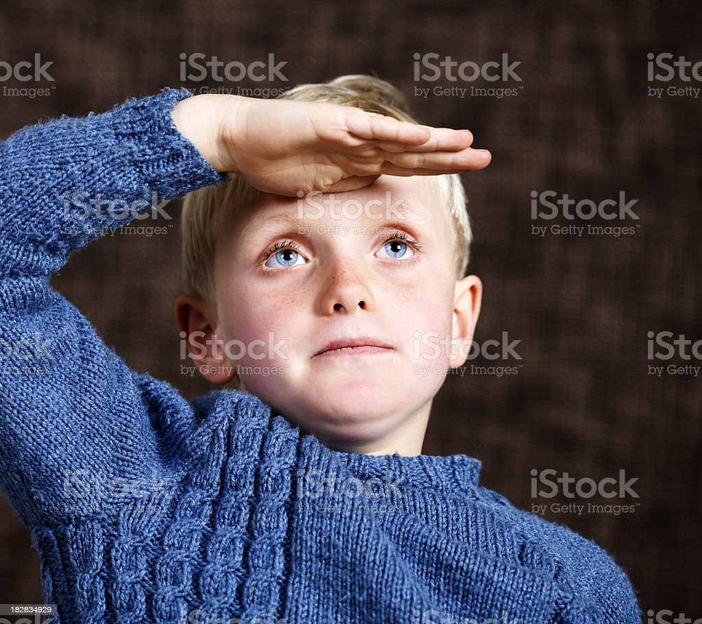 Seven-year-old blond boy looks into distance royalty-free stock photo