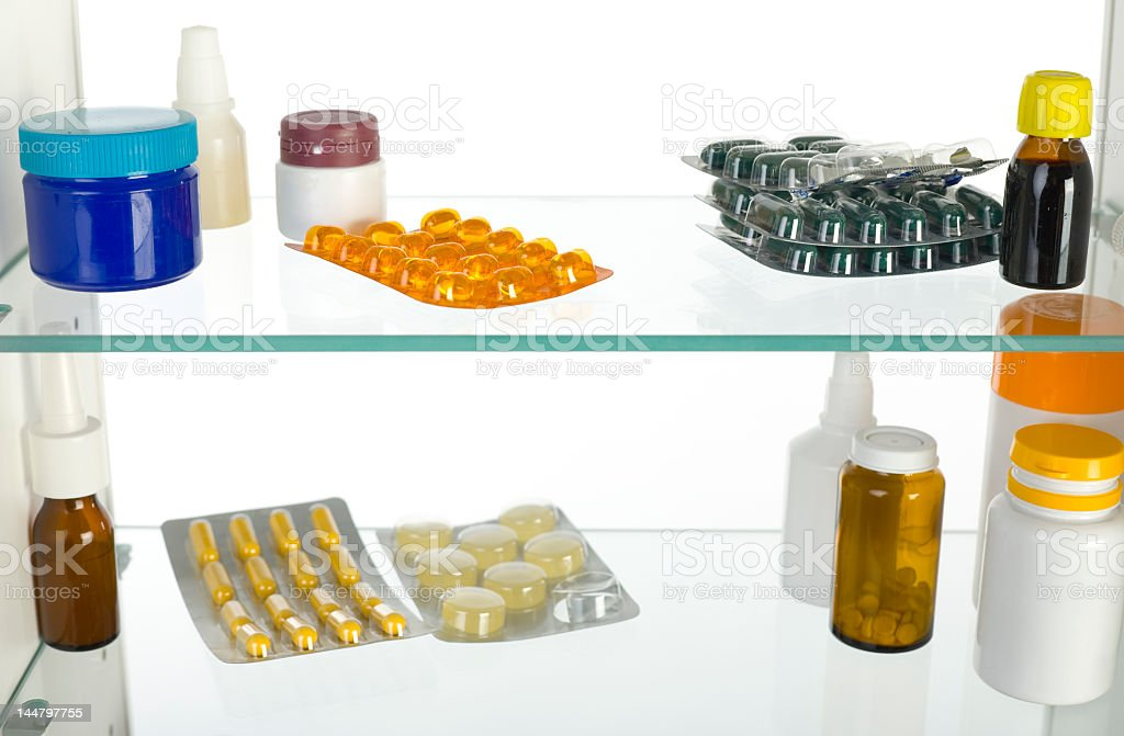 Several blister packs and vials in a medicine cabinet stock photo