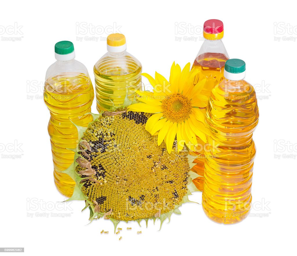 Several bottles of different sunflower oil and flowers of sunflo stock photo