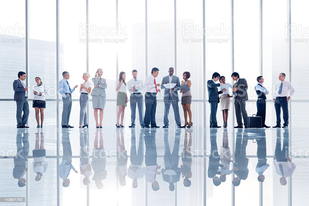 Several businesspeople working in a reflective office royalty-free stock photo