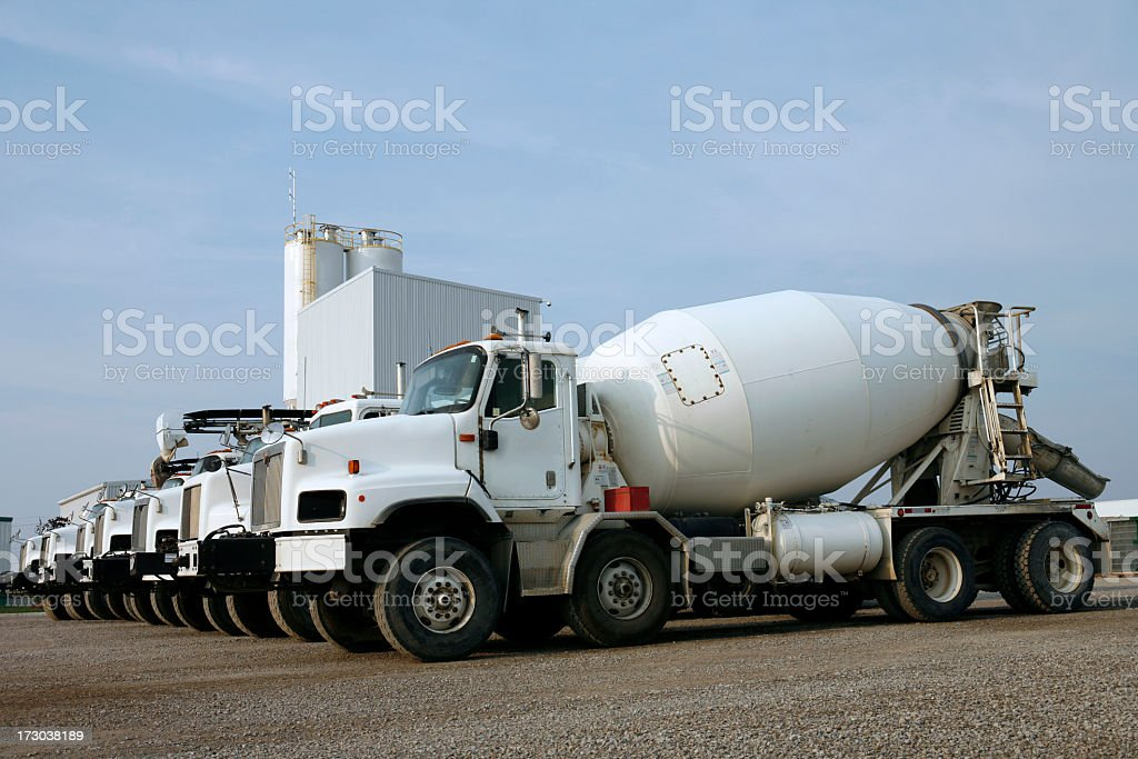 Several cement trucks lined up in a parking lot stock photo