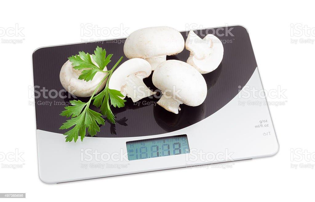 Several champignon mushroom on digital kitchen scale stock photo
