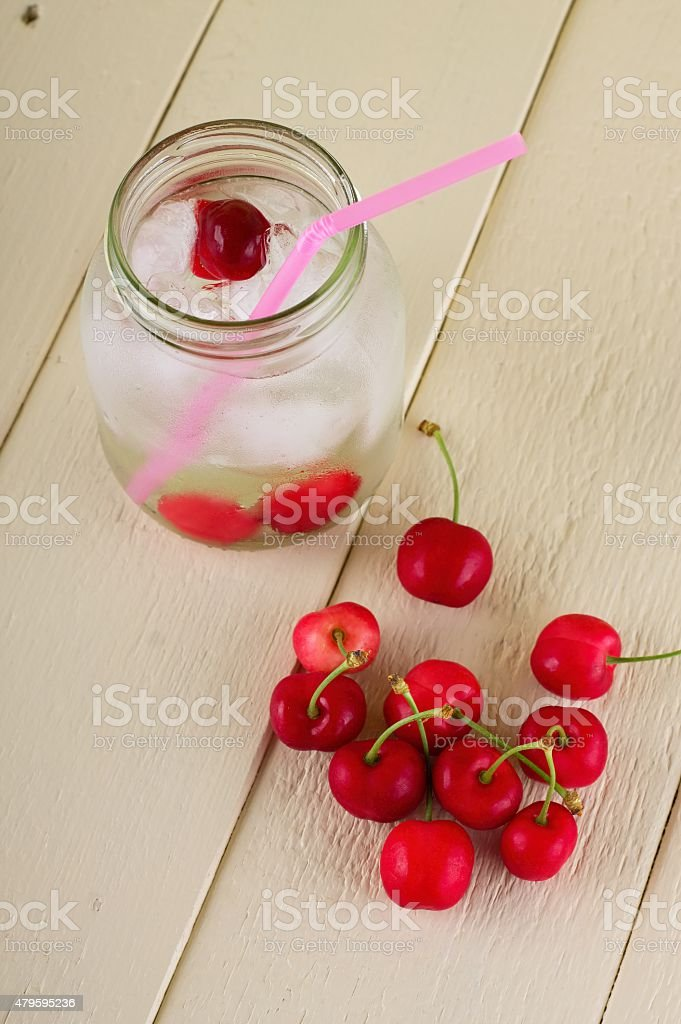 Several cherries next two fruit drink in a jar stock photo