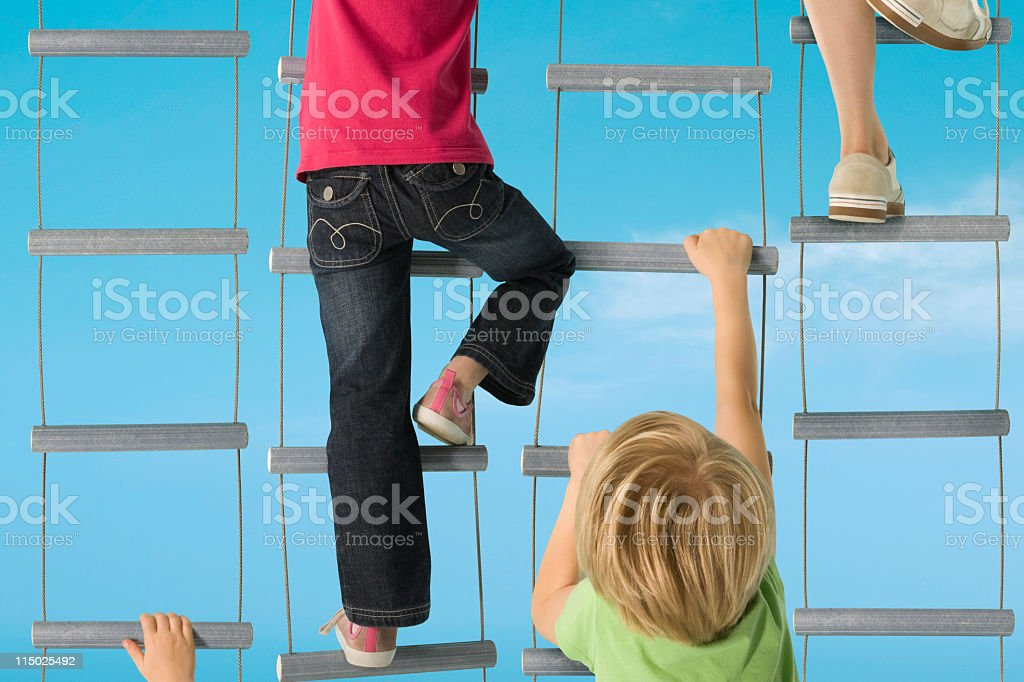 Several children going up hanging stairs in a race stock photo