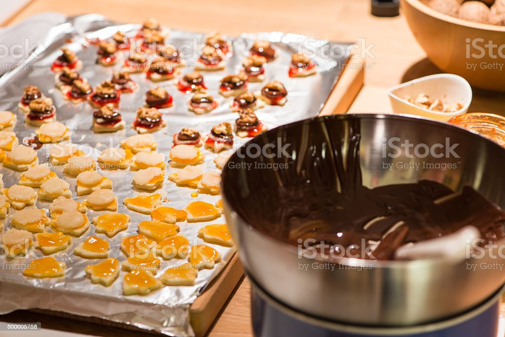 several christmas cookies on wooden table while baking stock photo