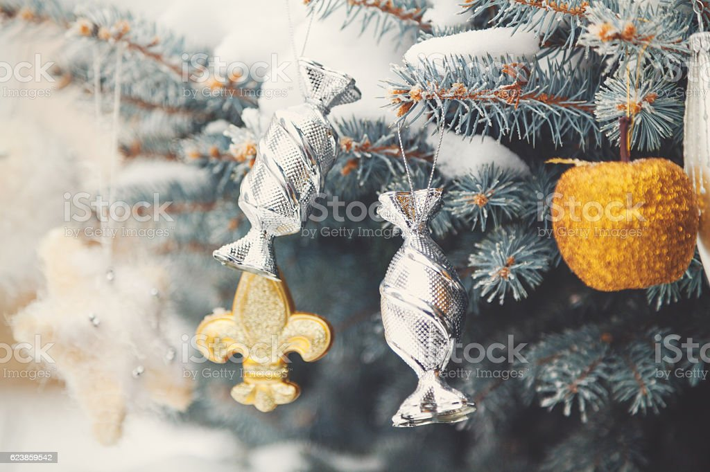Several Christmas toys weigh on snow-covered branches  Christmas tree stock photo
