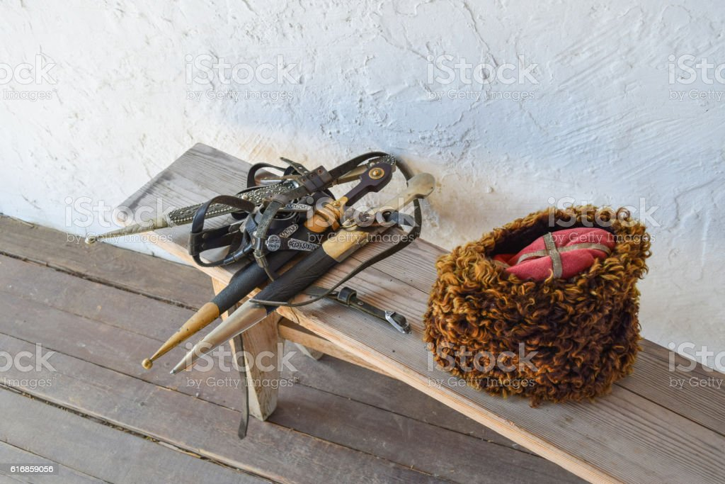 Several daggers on a bench near a Cossack hat stock photo