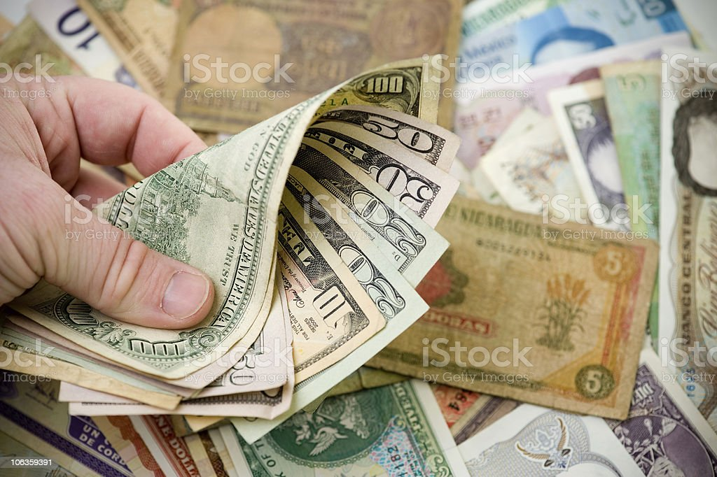 Several denominations of US dollars in a persons hand stock photo