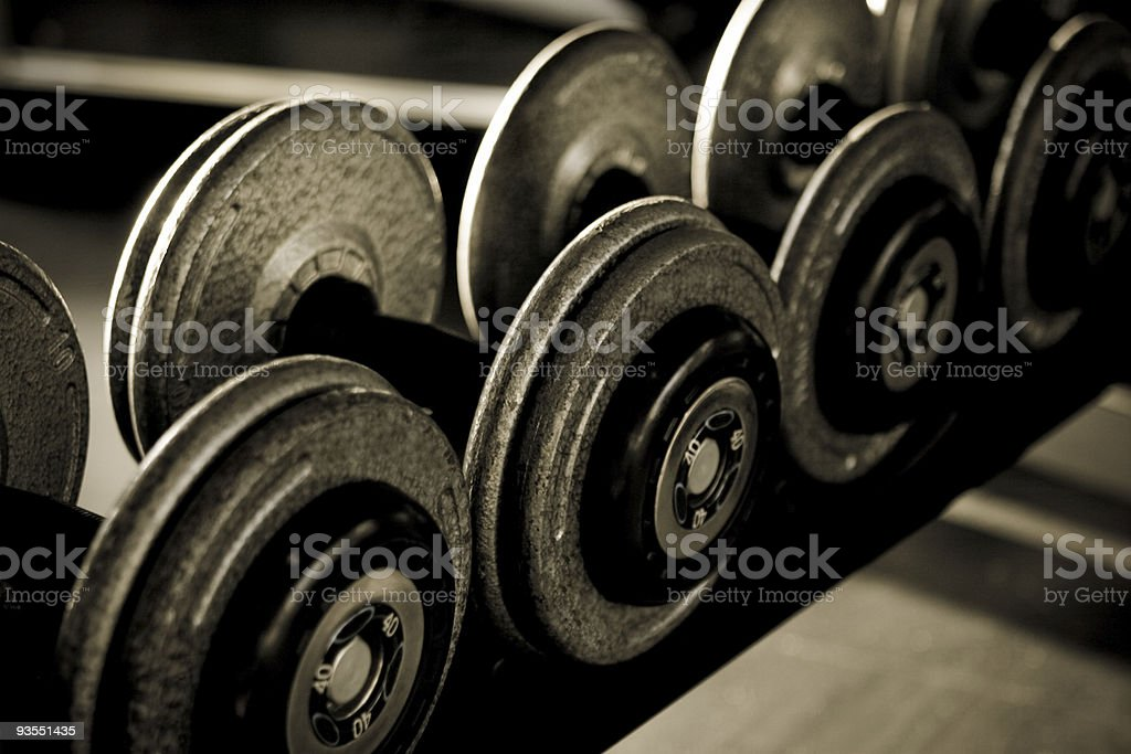 Several dumbbells resting on a rack in black and white royalty-free stock photo