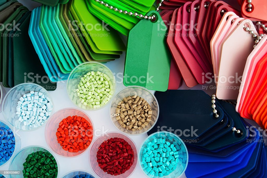 several dyed plastic polymer granulates stock photo