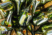 Several empty green bottles stacked in a wicker basket