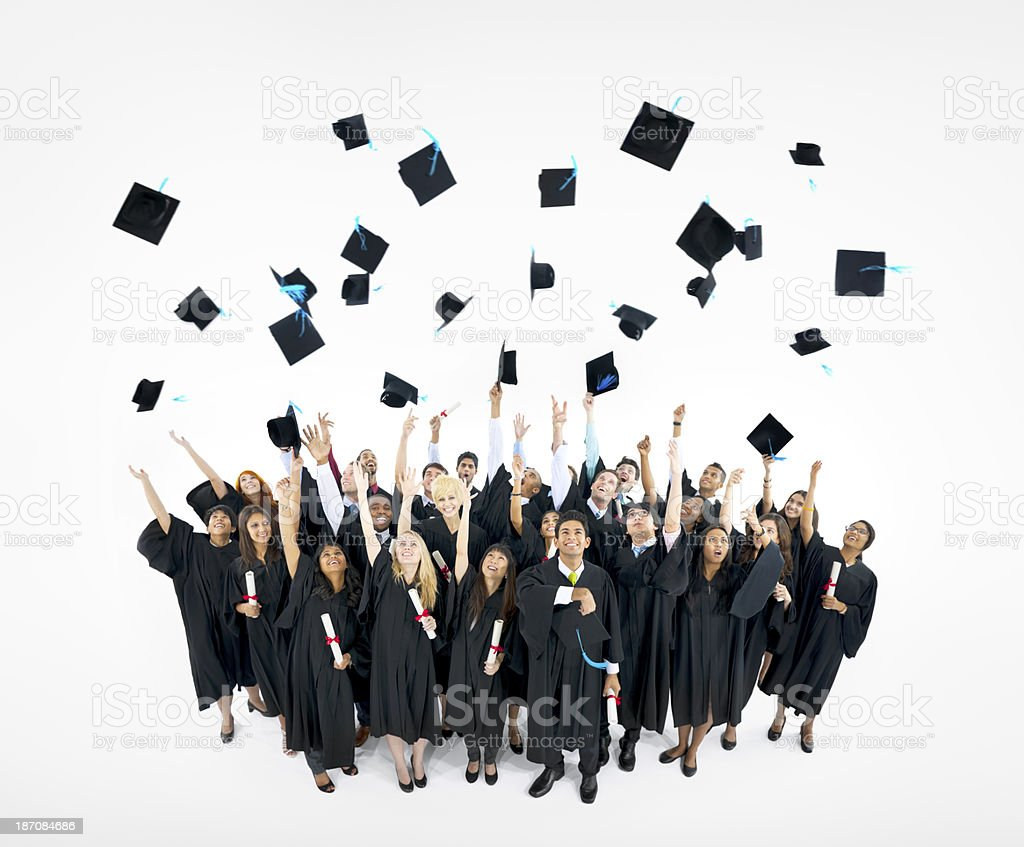 Several graduates tossing their hats in the air royalty-free stock photo