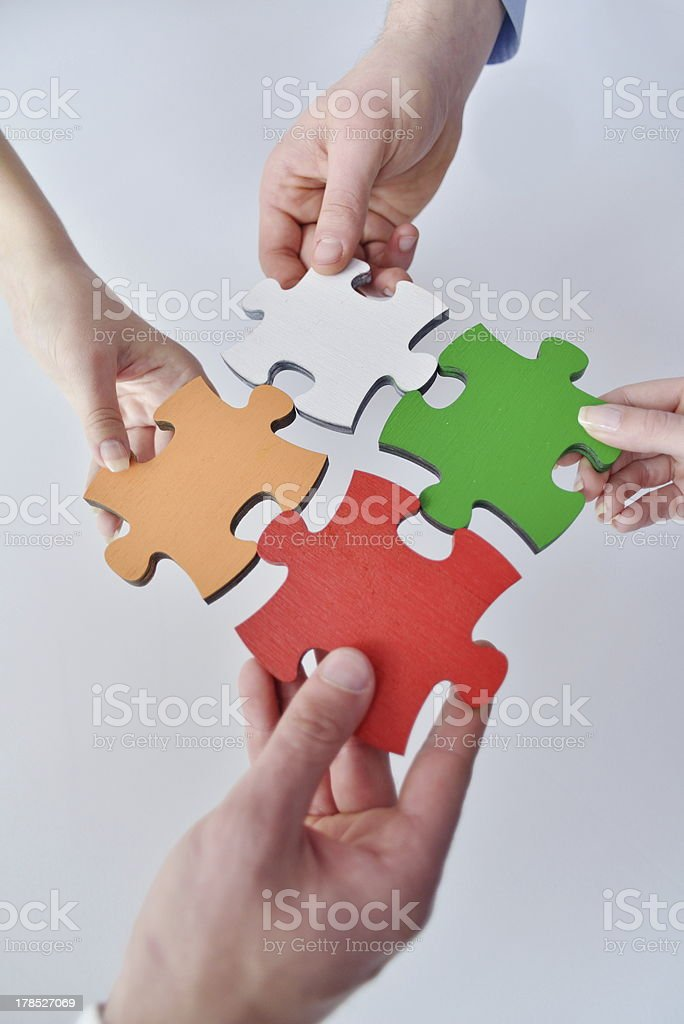 Several hands assembling jigsaw puzzle royalty-free stock photo